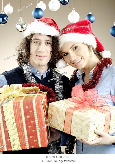 Portrait of a young woman and a man with presents wearing Christmas caps