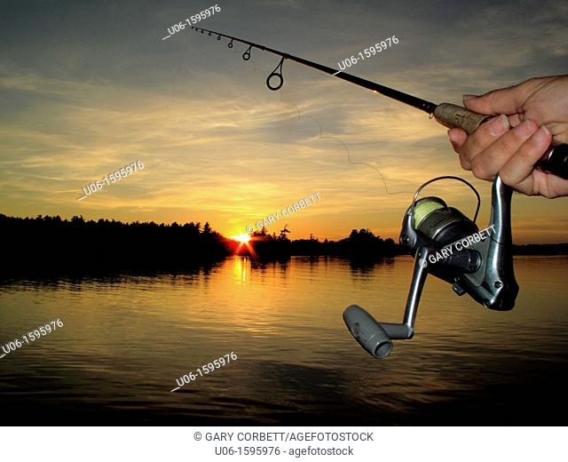 A fishing rod and reel with a sunset on a lake in background