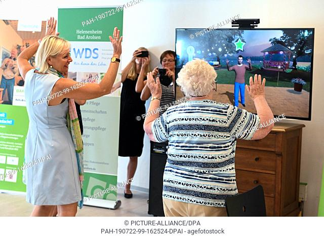 22 July 2019, Hessen, Bad Arolsen: The Hessian digital minister Kristina Sinemus (without party, l) makes a dance game in front of the game console in the...