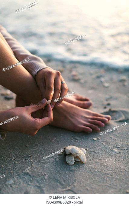 Woman playing with seashells on beach
