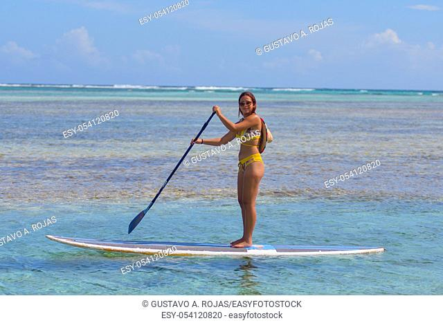 Young Hispanic woman using rowing at left side on paddle board or SUP at Caribbean beach with turquoise clear calm waters