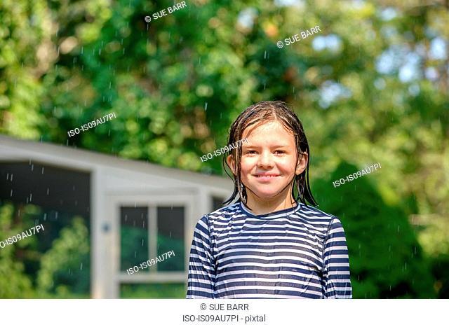 Portrait of girl in garden, wet hair, smiling
