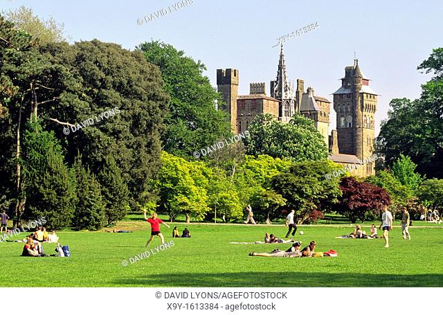Cardiff Castle rises behind Bute Park  Cardiff city centre, Wales, UK  Students and lunch break office workers relaxing  Summer