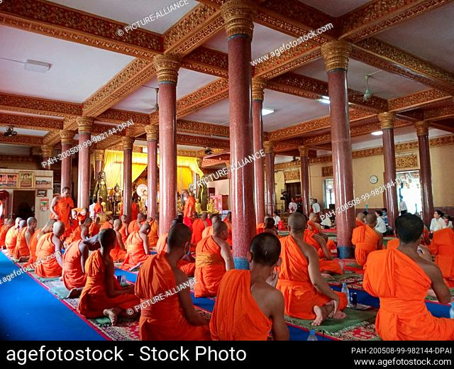 06 May 2020, Cambodia, Phnom Penh: Buddhist monks sit in rows in the temple complex Wat Ounalom to celebrate Visakha Bucha, the Buddha Day