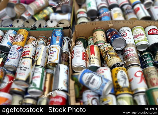 A pile of old beer cans in a box at a flea market