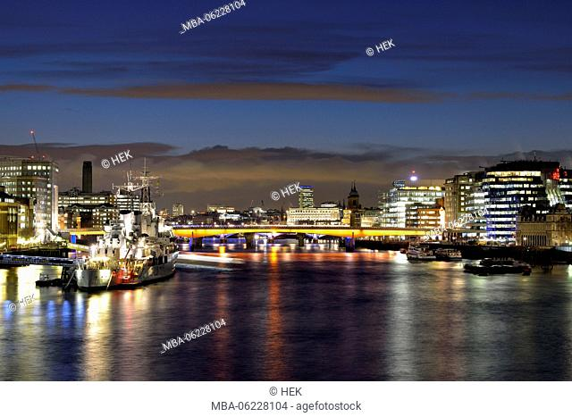London skyline on the River Thames with view to the illuminated London Bridge and the warship HMS Belfast Museum