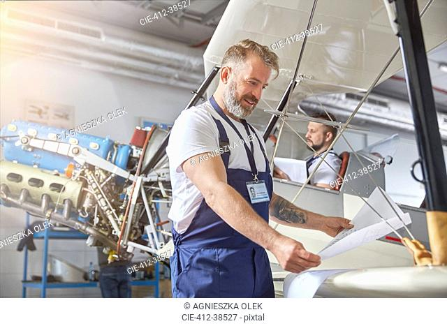 Male mechanical engineer reviewing plans at airplane in hangar