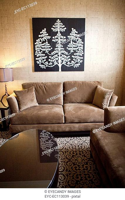 View of a living room with sofa set, coffee table, lit lamp and painting mounted on wall