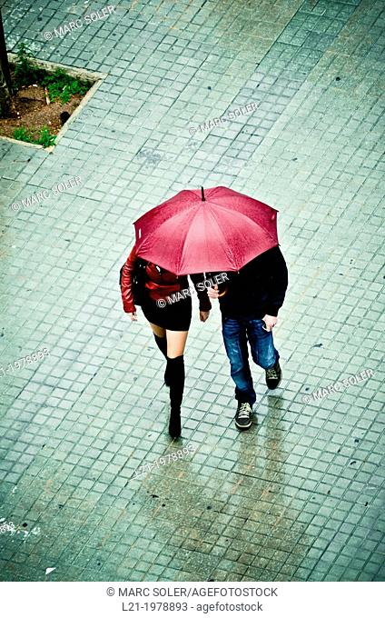 Couple, man and woman, walk down the street under an umbrella. Viewpoint from above. Barcelona, Catalonia, Spain
