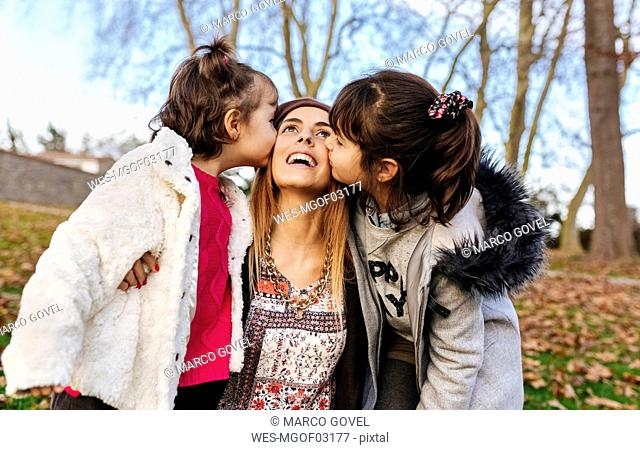 Happy mother kissed by her little daughters