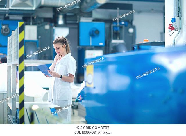 Woman working at machinery in laundry