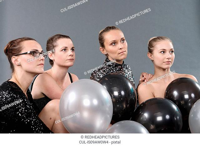Young women with black and white balloons, grey background