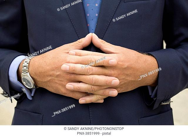Close-up of man's hands in suit with fingers crossed in front