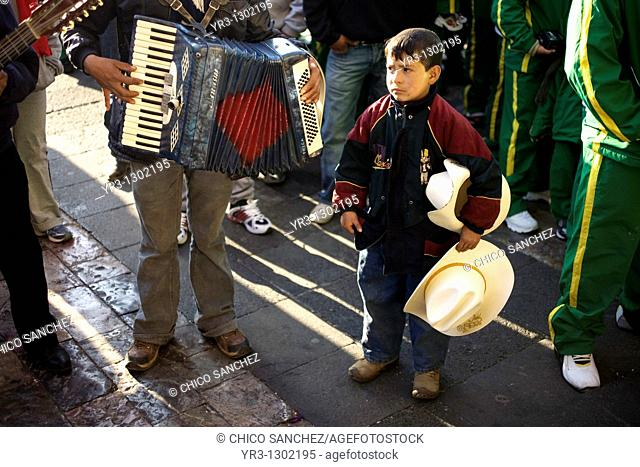 A boy looks at a musician playing the accordion outside the Our Lady of Guadalupe Basilica in Mexico City, December 10, 2008  Hundreds of thousands of Mexican...