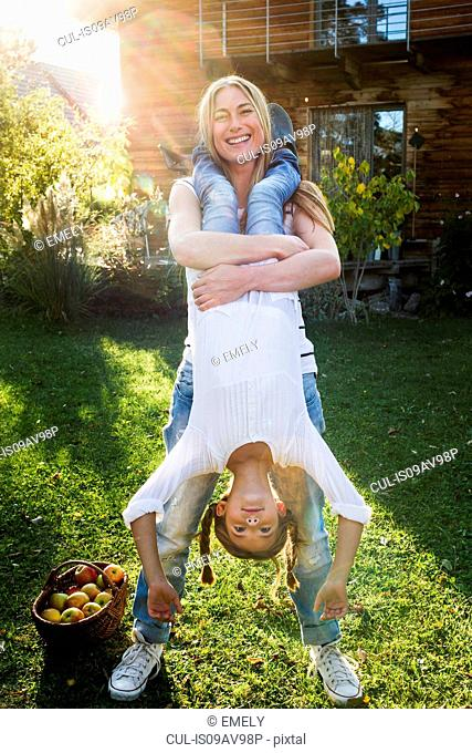 Mother lifting daughter upside down in garden