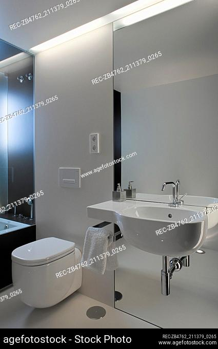 Wall mounted washbasin set on mirrored wall next to toilet with concealed cistern