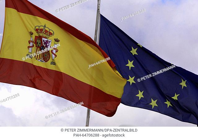 Spains national flag on the Arrecife Airport on the Canary Island Lanzarote, Spain, 10 October 2015. Next to it is the flag of the European Union (R)