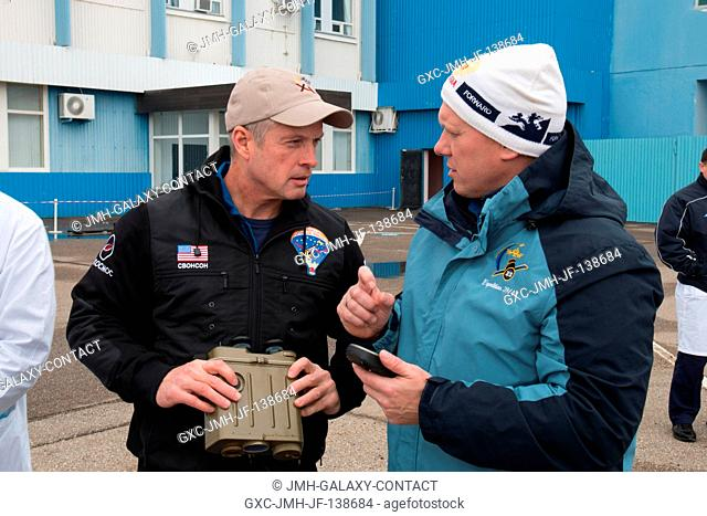 Outside the Integration Facility at the Baikonur Cosmodrome in Kazakhstan, Expedition 3940 Flight Engineer Steve Swanson of NASA (left) and Flight Engineer Oleg...