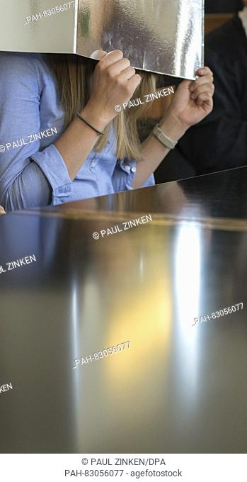 Esther S., who is accused of homicide, holds a piece of paper in front of her face in a courtroom of the Landcourt in Berlin, Germany, 24 August 2016
