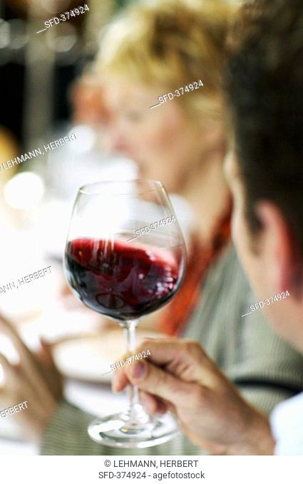 Man swirling a glass of red wine