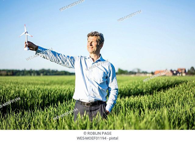Businessman standing in grain field, holding miniature wind wheel