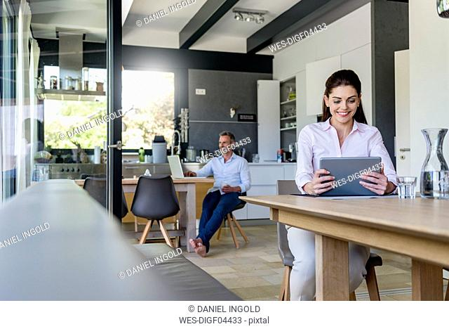 Smiling woman at home using a tablet at table with man in background using laptop