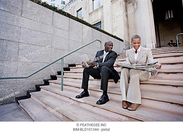 Business people unwinding on urban stairs