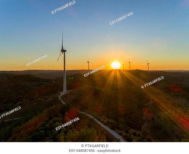 Aerial Wind farm turbines silhouette at sunset. Clean renewable energy power generating windmills. Algarve countryside. Portugal