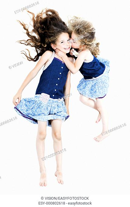 two caucasian little girls kissing afection isolated studio on white background