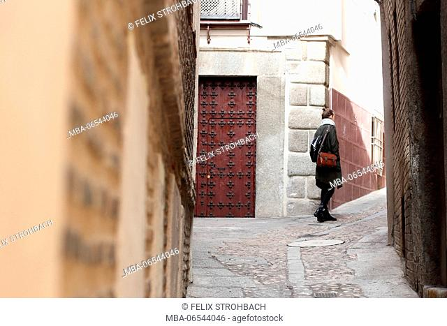 A young woman exploring the small lanes of Toledo