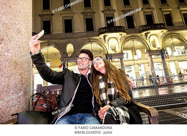 Caucasian couple sitting on urban bench posing for cell phone selfie