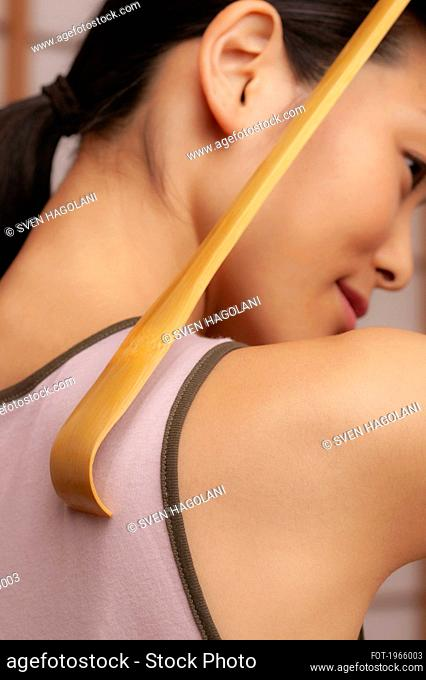 Close up young woman using wooden back scratcher