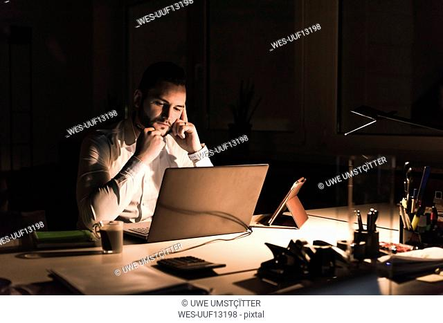 Pensive businessman working on laptop in office at night