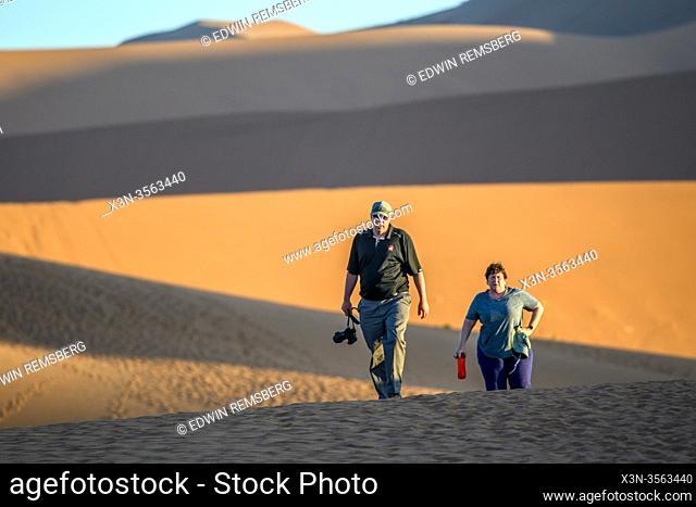 Hikers walking through the desert in Sossusvlei , Namib-Naukluft National Park , Namibia