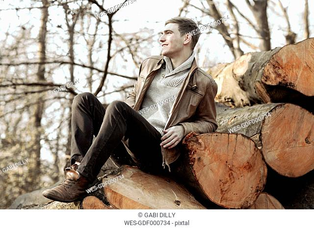 Young man sitting on stack of tree trunks