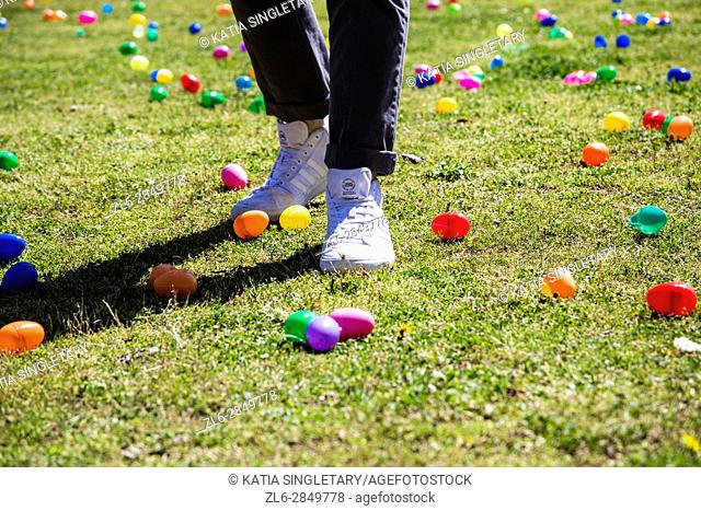 Young man with white tennis shoes and black skinny jeans in the grass in the middle of Easter egg hunt at a festival outside, with food trucks, eggs on the lawn