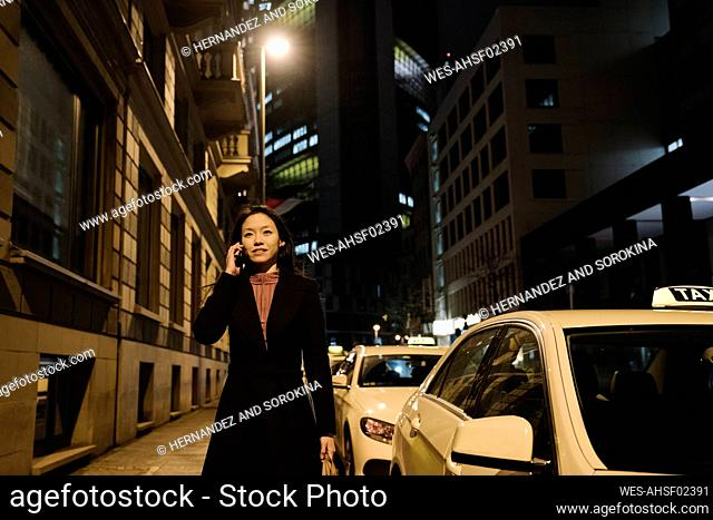 Young woman on the phone in the city at night, Frankfurt, Germany