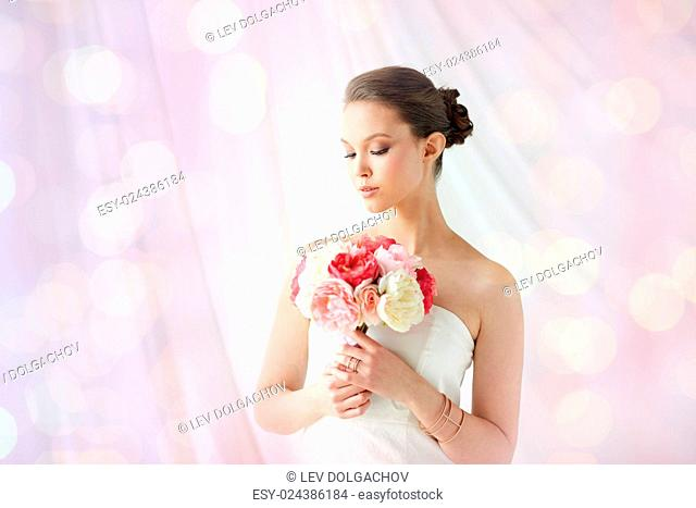 beauty, jewelry, people and luxury concept - beautiful asian woman or bride in white dress with peony flower, golden ring and bracelet over holidays lights...