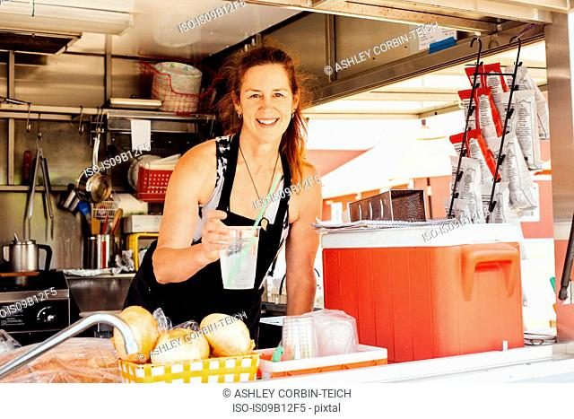 Portrait of woman handing drink at hatch of food stall trailer