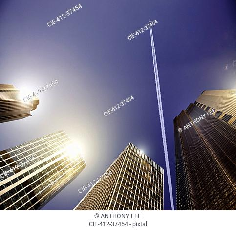 Airplane and vapor trail in blue sky above highrise buildings, travel concept