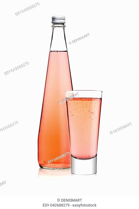 Bottle and glass of sparkling pink soda drink lemonade on white background