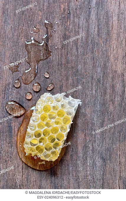 Honeycomb and honey over old wooden table