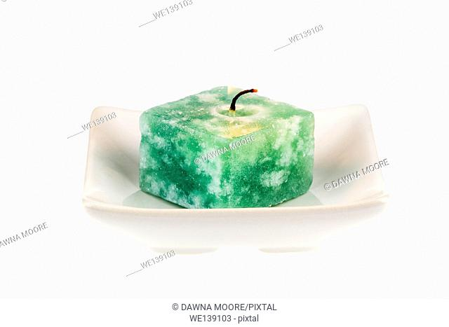Candle on a plate isolated on a white background