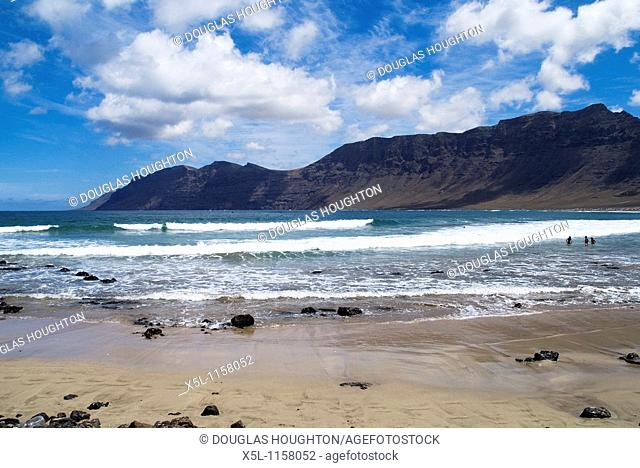 Playa de Famara FAMARA LANZAROTE Bathers in surf waves sandy beach El Risco de Famara sea cliffs and bay
