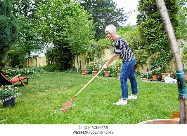 Woman raking on meadow in the garden