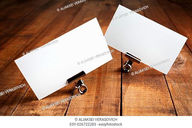 Photo of blank business cards on vintage wood table background. Mock up for ID. Blank template for branding identity for designers