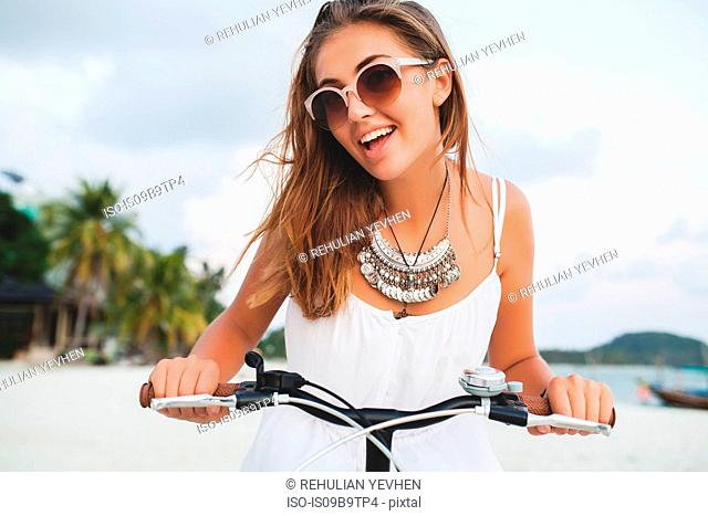 Portrait of young woman holding bicycle handlebars on sandy beach, Krabi, Thailand
