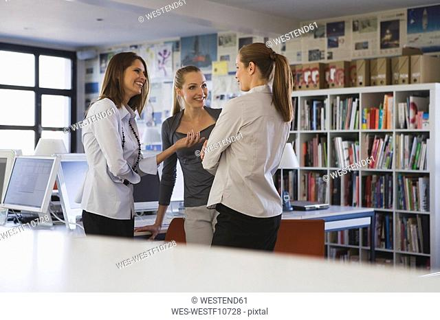 Young women in office talking
