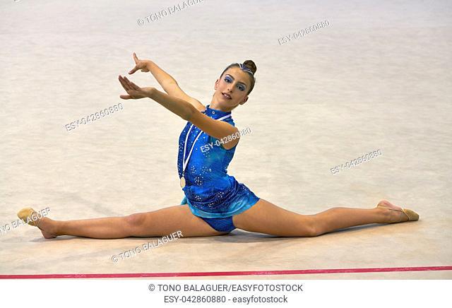 medalist gymnastics teen girl holding medal with blue dress