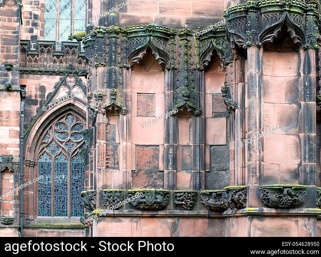 details of ornately carved medieval stonework with niches and animals on the facade of chester cathedral